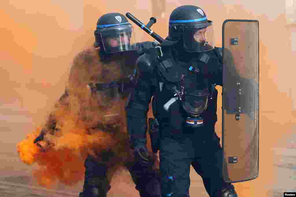 French CRS riot police face off with protesters during a demonstration against government reforms in Nantes.