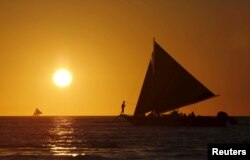 FILE - Tourists catch a glimpse of the sunset while sailing along the island of Boracay, central Philippines January 17, 2016.