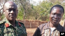 FILE - In this photo released by the Uganda People's Defense Force (UPDF), Ugandan Contingent Commander to the African Union Regional Task Force Col Michael Kabango, left, talks with a man in UPDF custody said by the UPDF to be the wanted Lord's Resistance Army (LRA) commander Dominic Ongwen, right, in the Central African Republic.