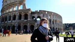 Para turis mengenakan masker saat mengunjungi Coliseum di Roma, Italia (foto: ilustrasi).