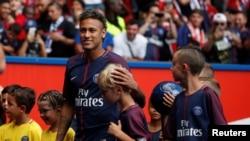 Neymar tient un enfant avant le match de PSG contre SC Amiens à Paris, 5 août 2017.