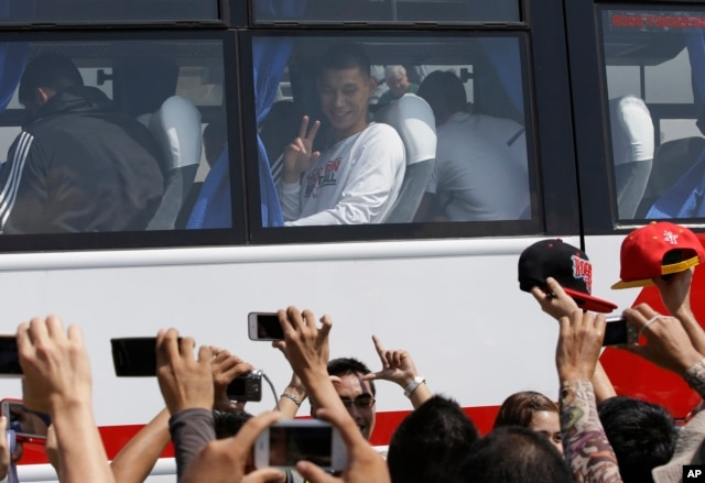 The Houston Rockets' Jeremy Lin waves to Filipino fans upon arrival on Oct.7, 2013, at the Ninoy Aquino International Airport south of Manila, Philippines, for the first NBA game ever played in the basketball-crazy Southeast Asian nation.