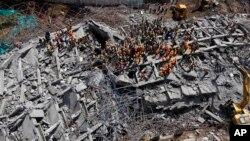月29日印度救援人員在南部泰米爾納德邦一座倒塌的建築現場搜尋倖存者。