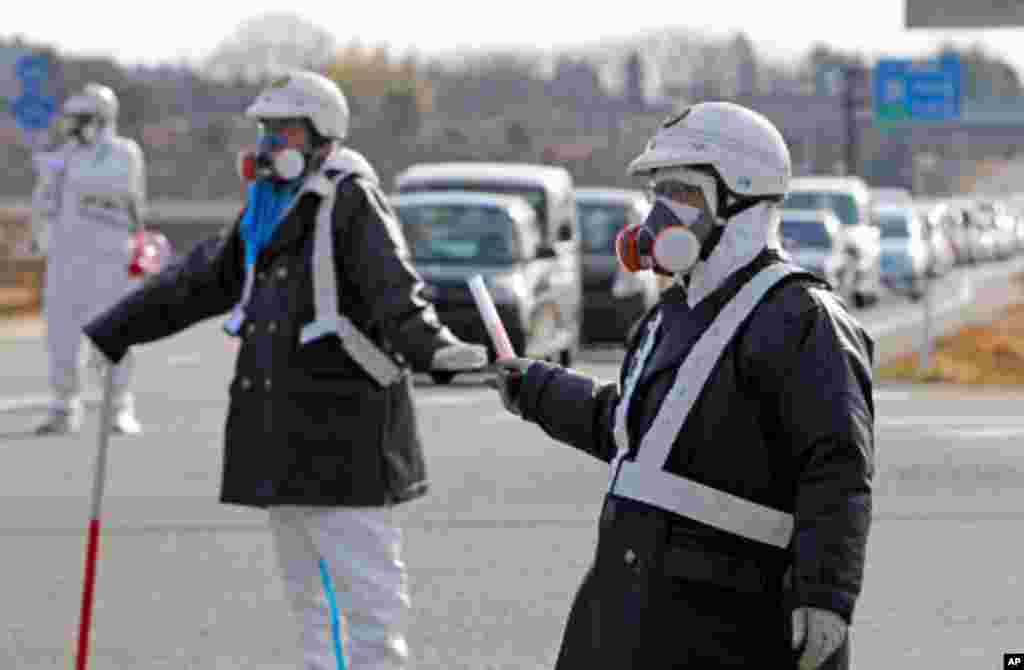 Police officers wearing respirators guide people to evacuate away from the Fukushima Daiichi nuclear plant following an evacuation order for residents who live near the plant after an explosion in Tomioka Town in Fukushima Prefecture, March 12, 2011