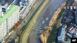 In this image made off a video released by Miyagi Prefectural Police, water rushes up Sunaoshi river in Tagajo, Miyagi prefecture, Nov. 22, 2016.