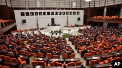 Lawmakers debate before Turkey's parliament to approve a motion that gives the government new powers to launch military incursions into Syria and Iraq and to allow foreign forces to use its territory for possible operations against the Islamic State group
