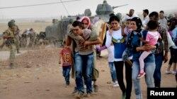 지난 20일 시리아 쿠르드족 난민들이 이슬람 수니파 무장단체 ISIL을 피해 터키 국경을 넘고 있다.