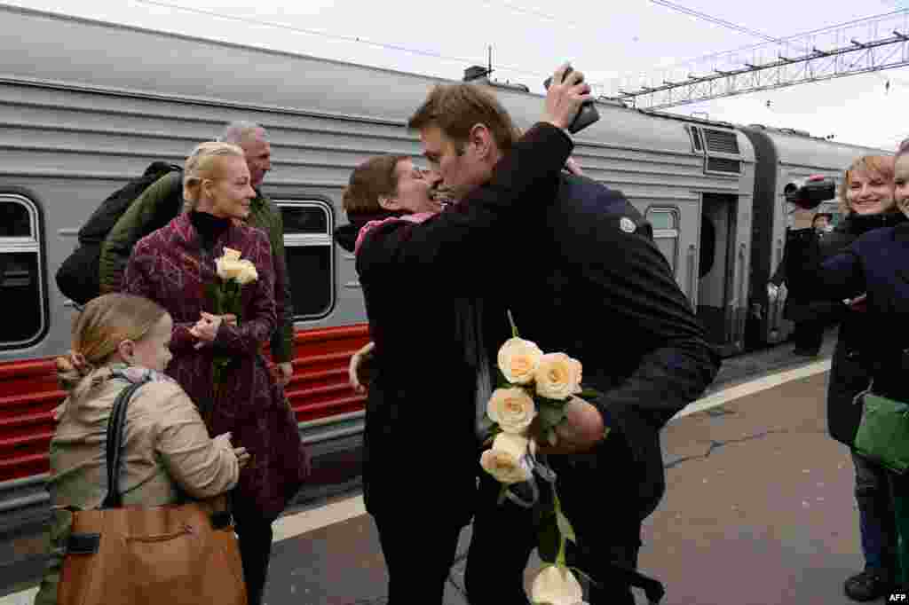 Russian opposition leader Alexei Navalny (C, R) is greeted by a supporter upon his arrival with his wife Yulia (2ndL) at a railway station in Moscow after his trial in the provincial northern city of Kirov. A court in Kirov converted his five-year sentence into a suspended term.