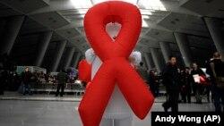 """Seorang relawan membawa """"Pita Merah"""", simbol kesadaran HIV/AIDS memperingati hari Aids, 1 Desember 2009 di Stasiun Kereta Api Beijing, China. (Foto: dok)."""