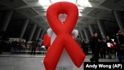 Imagem de arquivo: Voluntário exibe o símbolo da luta contra o SIDA numa estação de comboio em Pequim, China.