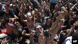 "Yemeni protesters, their faces colored with their national flag and Arabic writing that reads ""stop killing the innocent"", chant anti-government slogans during a demonstration demanding the resignation of President Ali Abdullah Saleh in Sana'a, October 11"
