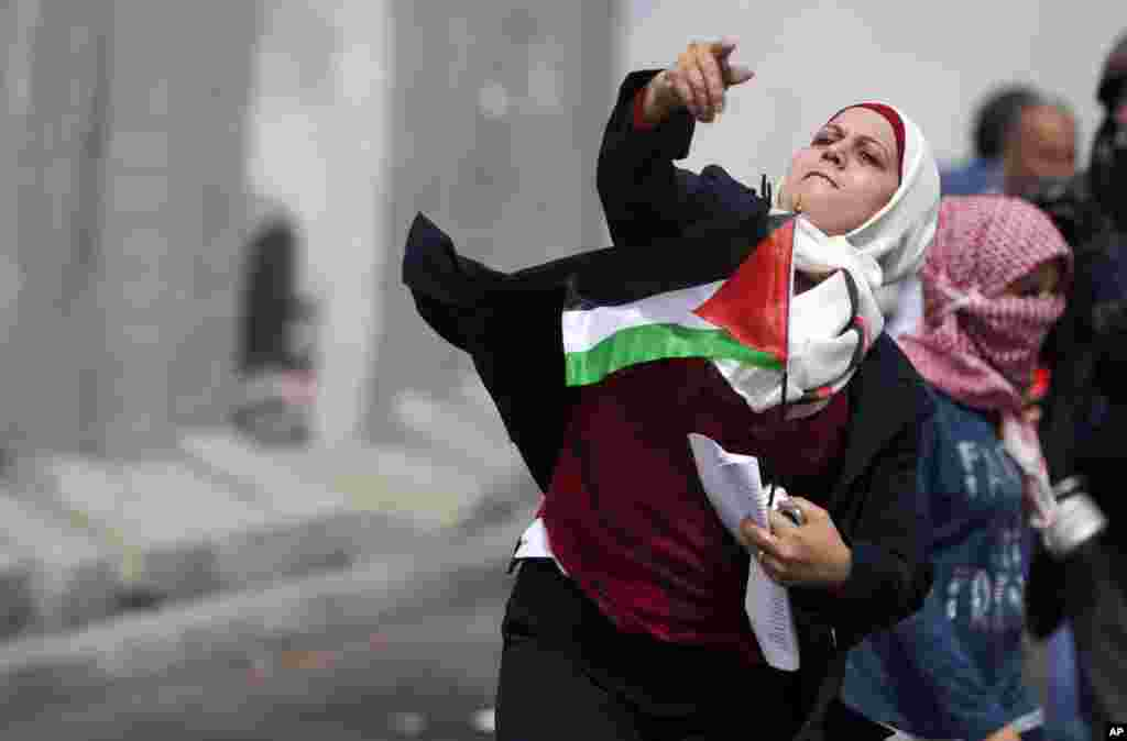 A Palestinian women throws a stone towards Israeli troops at Qalandia checkpoint between Jerusalem and the West Bank city of Ramallah. Palestinian women marked International Women's Day by marching to the checkpoint where clashes broke out with Israeli troops.