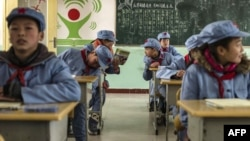 Children dressed in uniform gather in their classroom at the Beichuan Red army elementary school in Beichuan, southwest China's Sichuan province, To go with AFP story China-politics-education-history, Jan. 21, 2015.
