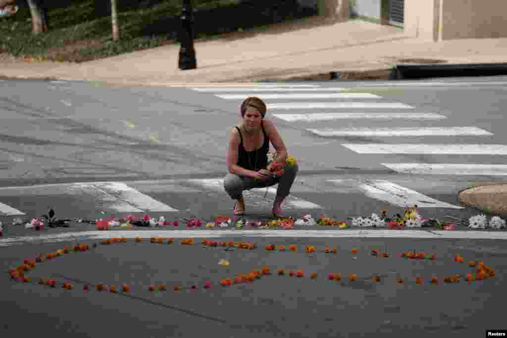 "A woman kneels at a makeshift memorial for the victims of a car that plowed into counter-protesters after a ""Unite the Right"" rally organized by white nationalists in Charlottesville, Aug. 13, 2017."
