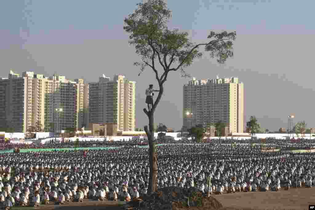 សមាជិកម្នាក់នៃសមាគមអ្នកស្ម័គ្រចិត្តជាតិដែលគោរពសាសនាហិណ្ឌូ ឃ្លាំមើលសកម្មភាពរបស់មនុស្សដែលអង្គុយនៅលើដី ពីលើដើមឈើ ក្នុងពេលបោះជំរុំរយៈពេលមួយថ្ងៃ នៅជាយក្រុង Pune រដ្ឋ Maharashtra ប្រទេសឥណ្ឌា។