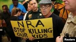 Seorang pria membawa tulisan memrotes asosiasi senjata AS (NRA) di Fort Lauderdale, Florida Kamis (15/2), sehari setelah terjadinya penembakan di sebuah SMU di Florida.