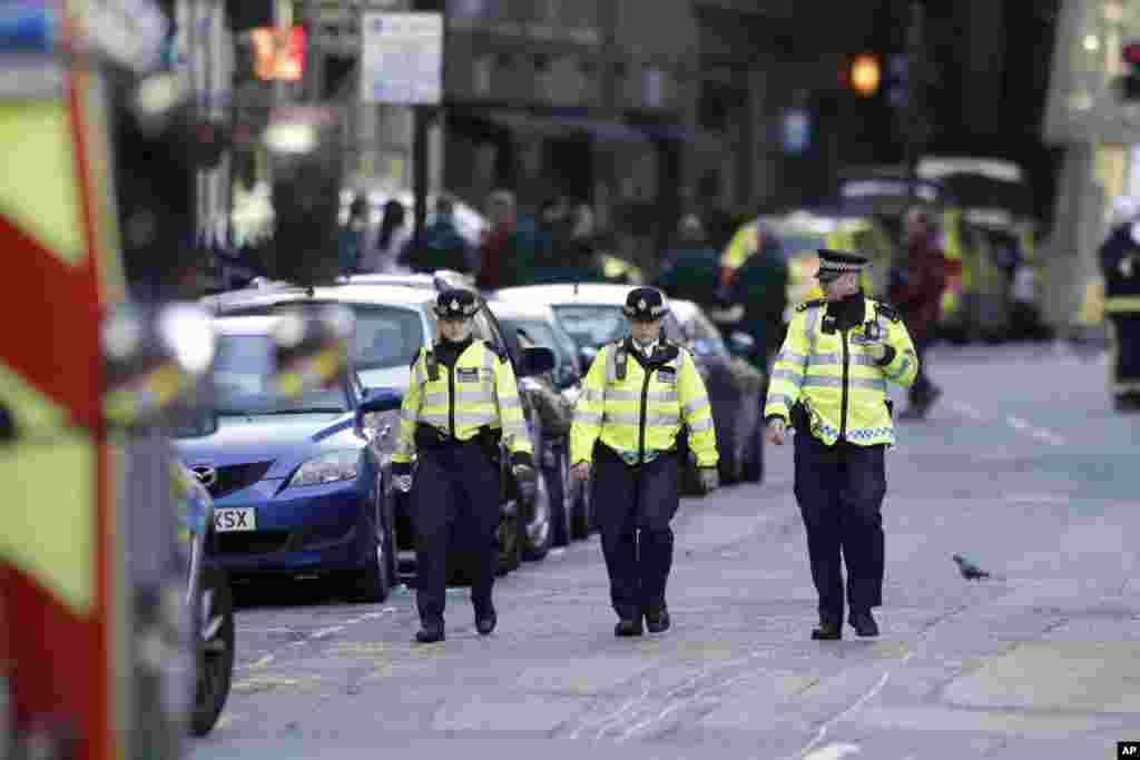 British police officers walk within a cordoned off area after an attack in the London Bridge area of London, June 4, 2017. Saturday night attackers killed several people in a series of vehicle and knife attacks before police shot them dead.