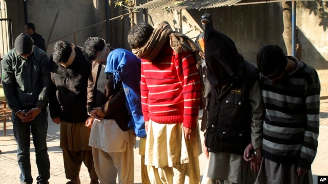 Pakistani suspects allegedly affiliated with the Islamic State group, wait to appear in the anti-terrorist court, in Gujranwala, Pakistan, on Dec. 29, 2015.