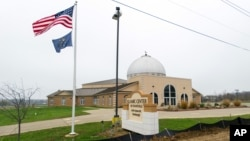 FILE - An American flag and the Indiana state flag fly in front of the Islamic Center of Evansville in Newburgh, Indiana, Nov. 30, 2015.