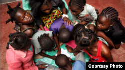 Children gather around a table at SOS Children's Villages Bangui. (Photo by Till Müllenmeister)