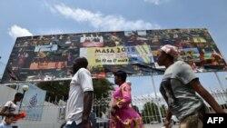 Quelques personnes marchent devant une pancarte publicitaire géante du Marché des Arts du Spectacle Africain d'Abidjan (Masa), à Abidjan, le 9 mars 2018.