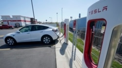 A Tesla charges at a station in Topeka, Kan., Monday, April 5, 2021. The president and the auto industry maintain the nation is on the cusp of a gigantic shift to electric vehicles and away from liquid-fueled cars, but biofuels producers and some of their