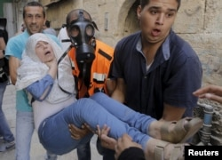 A Palestinian woman affected by tear gas is evacuated by medics during clashes between stone-throwing Palestinians and Israeli police on the compound known to Muslims as Noble Sanctuary and to Jews as Temple Mount in Jerusalem's Old City, Sept. 15, 20