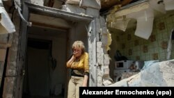 FILE - A local woman reacts next to her destroyed home after shelling in pro-Russian rebel-controlled Staromykhaylivka village near of Donetsk, Ukraine, 24 May 2016.