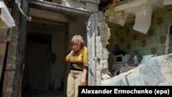 FILE - A local woman reacts next to her destroyed home after shelling in pro-Russian rebel controlled Staromykhaylivka village near Donetsk, Ukraine, May 24, 2016.