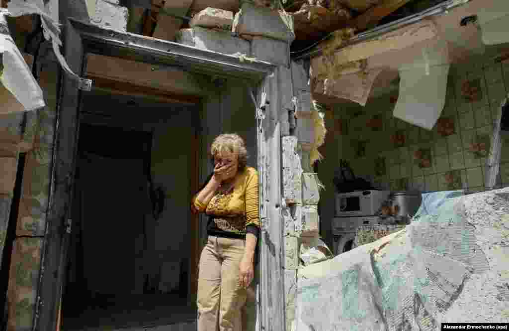 A local woman reacts as she looks at her destroyed home after shelling in the pro-Russian rebel-controlled Staromykhaylivka village near Donetsk, Ukraine, 24 May 2016.