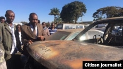 Nelson Chamisa inspecting a vehicle belonging to his party set on fire by unknown arsonists.