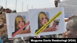 A protester holds up signs protesting against UNMISS head Hilde Johnson at a rally in Juba after South Sudanese government forces found weapons in a UN overland shipment.