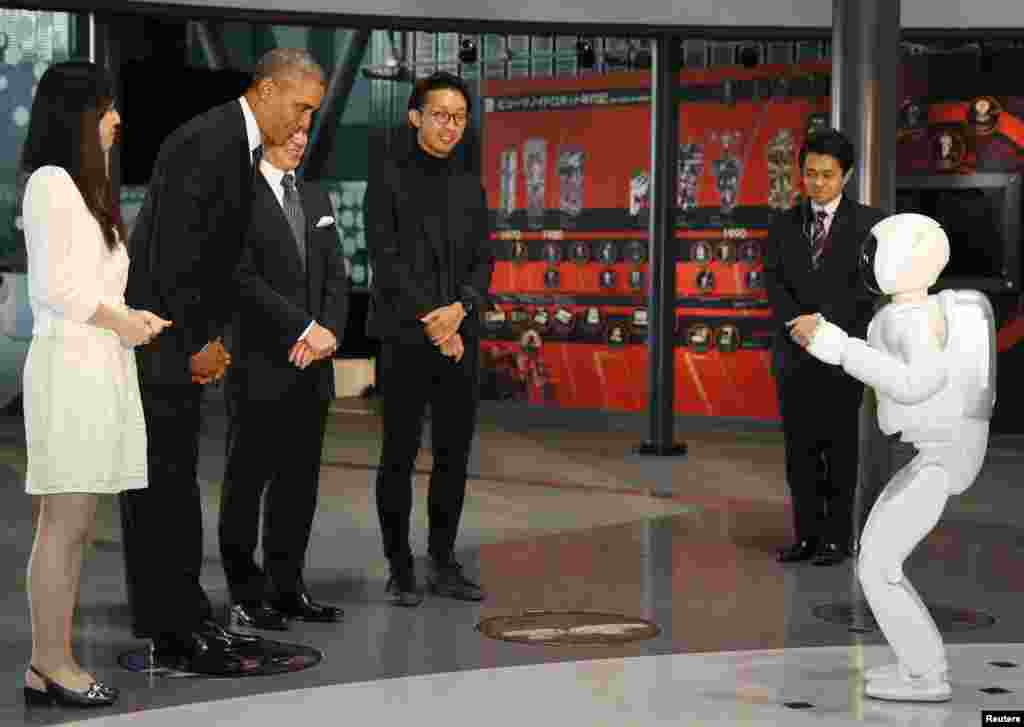 "U.S. President Barack Obama (2nd L) bows to ""Asimo"" the robot while visiting Miraikan or the National Museum of Emerging Science and Innovation, in Tokyo, Japan."