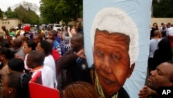 A group of mourners carrying a picture of South African leader Nelson Mandela, sing and dance outside his Johannesburg home, Dec. 6, 2013, after the freedom fighter passed away Thursday night after a long illness.