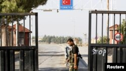 Seorang tentara Pembebasan Suriah berjaga di pintu gerbang terakhir perbatasan Suriah-Turki di Bab Al-Salam (22/5). Turki menutup perbatasan kedua negara menyusul memburuknya situasi keamanan di wilayah tersebut.