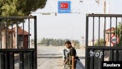 Pripadnik Slobodne sirijske armije ispred pogranične barijere koja vodi ka Turskoj, na prelazu Bab al-Salam