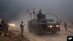 Kendaraan lapis baja Polisi Federal Irak melewati pos pemeriksaan di Qayyara, 50 kilometer dari selatan Mosul, Irak (26/10). (AP/Marko Drobnjakovic)