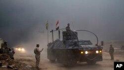 د عراق د فدرال پولیسو یو موټر په قئارا سیمه کې له پوستې تیریږي