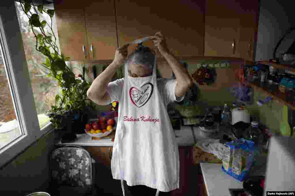 Jelena Petrovic puts on an apron as her husband returns with groceries.