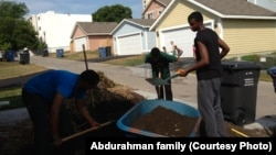 Zacharia Yusuf Abdurahman, right, does volunteer work for Habitat for Humanity in northern Minneapolis as a teenager.