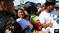 A woman and her child plead from the frantic crowd to be prioritized on an evacuation flight in Tacloban, central Philippines, Nov. 14, 2013.