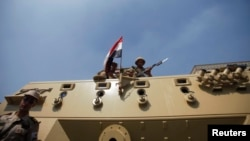 Members of the military hold their weapons atop a vehicle, on a road leading to the Raba El-Adwyia mosque square where supporters of Egypt's deposed President Mohamed Morsi are camping, in Cairo, July 4, 2013.