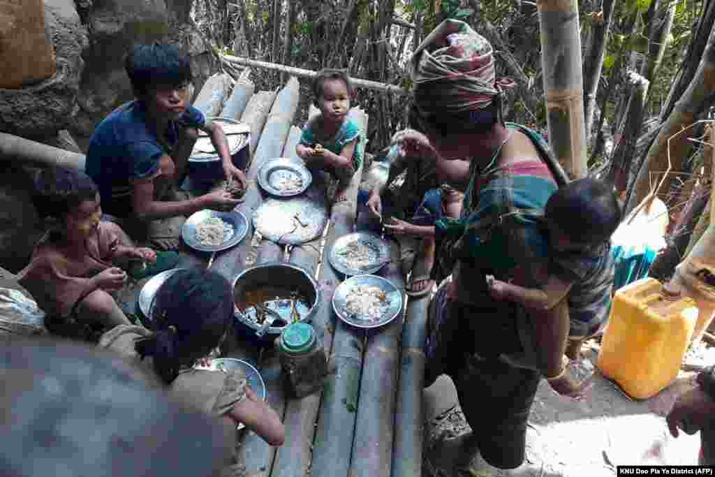 Karen villagers eat in the KNU Brigade 5 region in Myanmar's Karen state, after airstrikes by Myanmar military in the area following the February military coup.