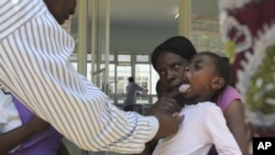 A doctor examines a child suffering from typhoid at a local infectious disease hospital in Harare, Zimbabwe, November15, 2011.