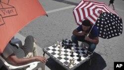 Estos dos neoyorquinos juegan ajedrez en la calle protegidos del ardiente sol por enormes sombrillas.
