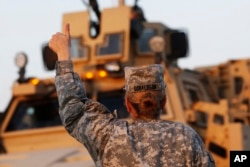 FILE - U.S. Army convoys are given the thumbs up from a fellow soldier after crossing into Kuwait during the last convoy out of Iraq.