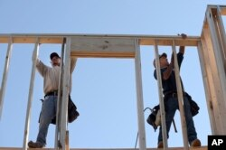 FILE - Construction workers David Rager, right, and Shawn White frame the upper floor of a home being built in Orlando, Florida, Feb. 13, 2015.