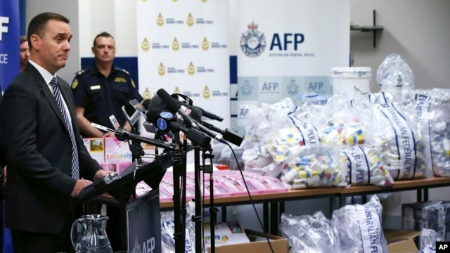 Commander Chris Sheehan from the Australian Federal Police stands by a display of confiscated drugs in Sydney, Monday, Jan. 15, 2016.