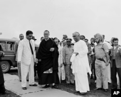 FILE - An unidentified Indian official, right, greets Tibetan spiritual leader Dalai Lama, in black robe, at a military camp on the border of Assam and the Northeast Frontier Agency area, April 18, 1959, shortly after the Dalai Lama's arrival in India.