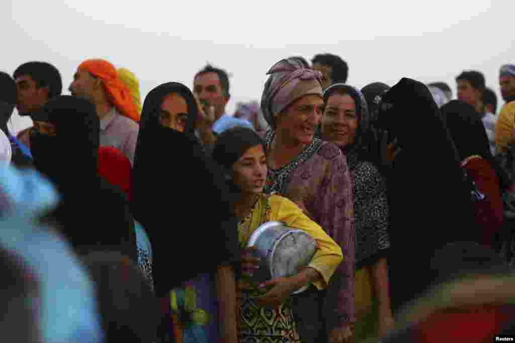 Iraqi refugees who fled from the violence in Mosul line up to receive free food during the holy fasting month of Ramadan, inside the Khazer refugee camp on the outskirts of Irbil, Iraq, June 29, 2014.
